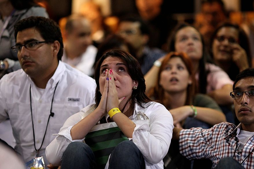 Supporters of opposition presidential candidate Henrique Capriles react while hearing official results in Caracas, Venezuela, on Sunday, Oct. 7, 2012. Venezuela's electoral council said late Sunday that President Hugo Chavez had won re-election, defeating challenger Henrique Capriles. (AP Photo/Ariana Cubillos)