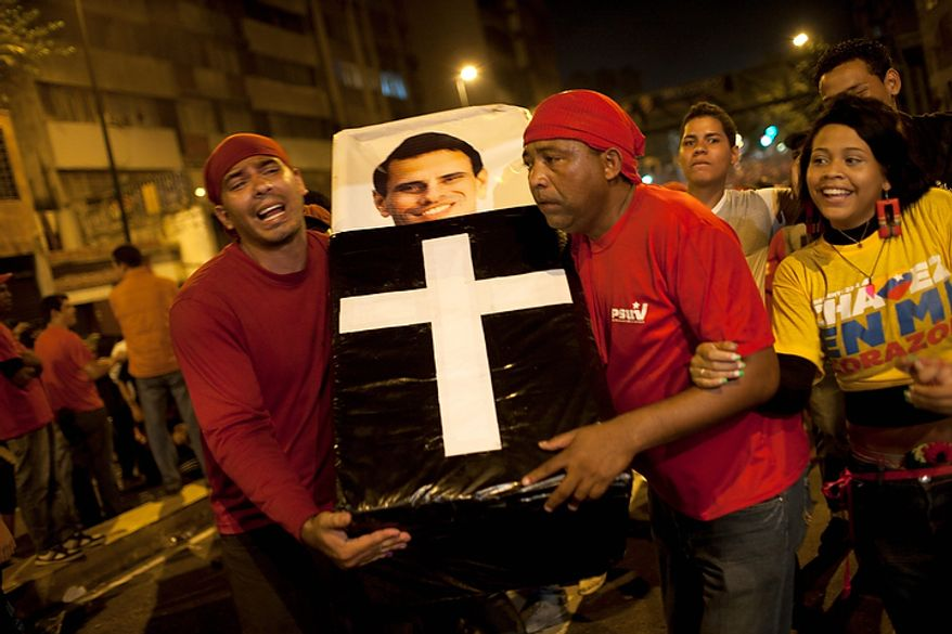 Supporters of Venezuelan President Hugo Chavez perform a mock funeral for opposition candidate Henrique Capriles as they celebrate in downtown Caracas, Venezuela, on Sunday, Oct. 7, 2012. Mr. Chavez won re-election and a new endorsement of his socialist project Sunday, surviving his closest race yet after a bitter campaign against Mr. Capriles. (AP Photo/Ariana Cubillos)