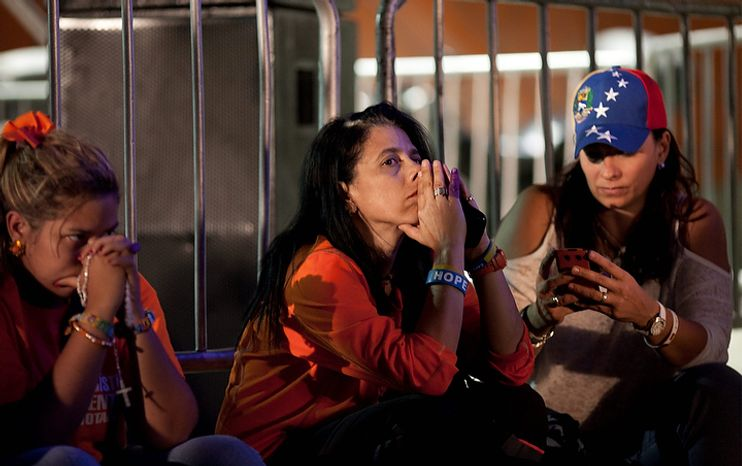 Supporters of opposition presidential candidate Henrique Capriles wait for election results at the campaign headquarters in Caracas, Venezuela, on Sunday, Oct. 7, 2012. Venezuela's electoral council said President Hugo Chavez had won re-election, defeating Mr. Capriles. (AP Photo/Ariana Cubillos)