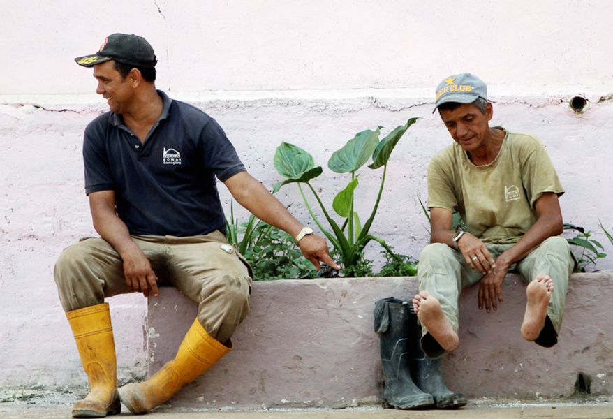 A sugar plant worker shows his feet to a fellow worker at the Brasil sugar processing plant in Jaronu, Cuba. (Associated Press)