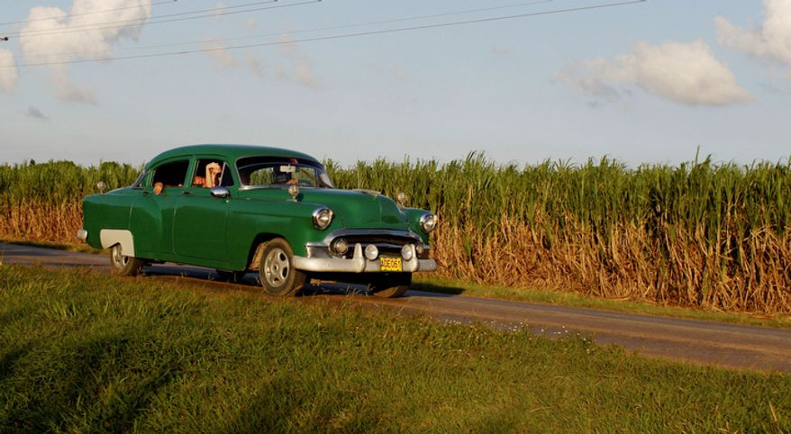 People drive a classic American car past a sugar cane field in Camaguey, Cuba, on Sept. 8, 2012. (Associated Press)