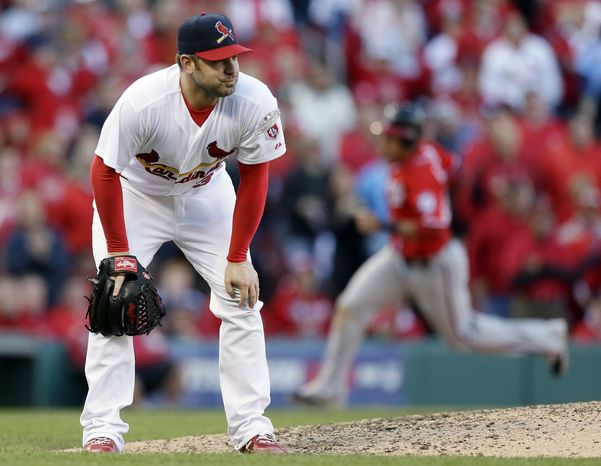 St. Louis Cardinals pitcher Marc Rzepczynski, foreground, reacts after giving up a two-run single to Washington Nationals' Tyler Moore in eighth-inning action during Game 1 of the NLDS. Ian Desmond, background, rounds third on his way to scoring. (Associated Press)
