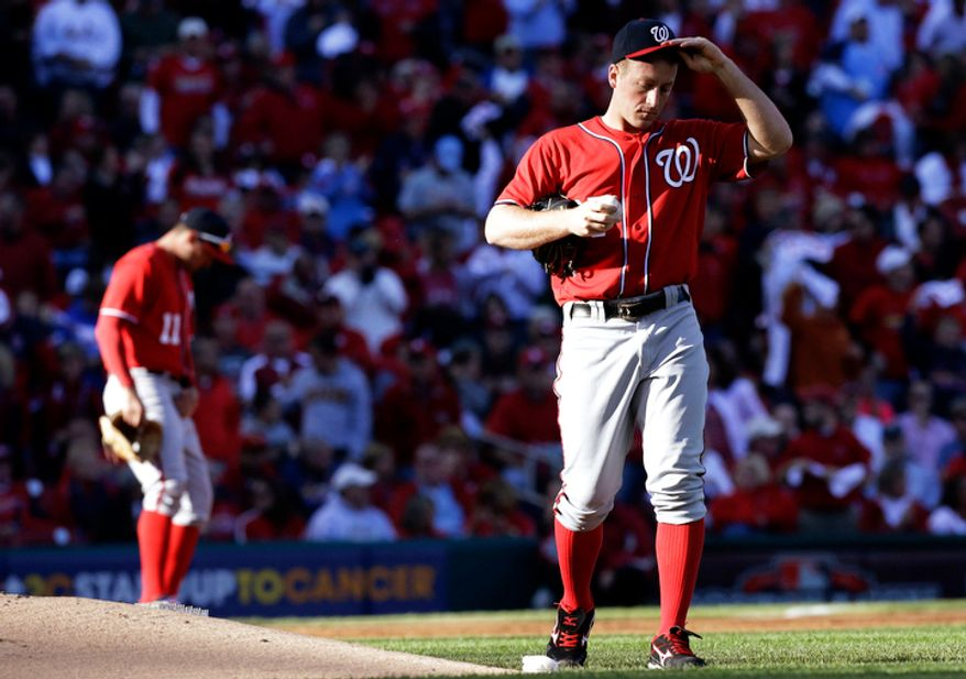 Washington Nationals starting pitcher Jordan Zimmermann, right, adjusts his cap after allowing a single to St. Louis Cardinals' Yadier Molina during the second inning of Game 2. (AP Photo/St. Louis Post-Dispatch, Chris Lee)
