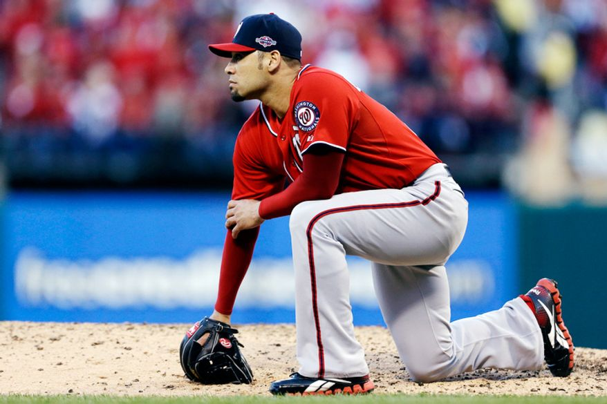 Washington Nationals relief pitcher Mike Gonzalez watches as a solo home run hit by St. Louis Cardinals' Carlos Beltran leaves the park during the sixth inning in Game 2. (AP Photo/Jeff Roberson)