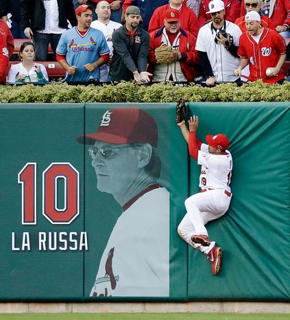 St. Louis Cardinals center fielder Jon Jay leaps at the wall to catch a fly ball off the bat of Washington Nationals' Danny Espinosa during the sixth inning of Game 2. (AP Photo/St. Louis Post-Dispatch, Chris Lee)