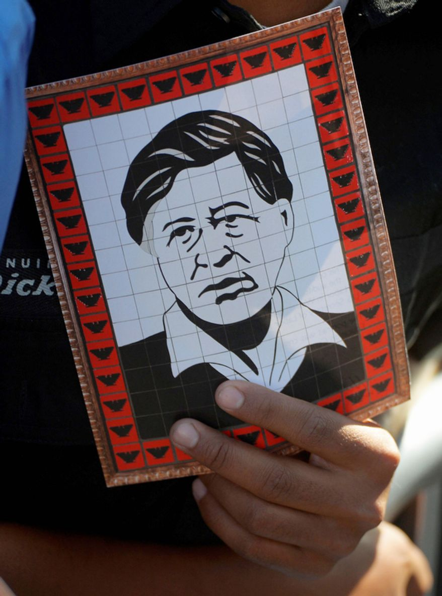 An attendee holds a picture of Cesar Estrada Chavez on Oct. 8, 2012, as President Obama announces the establishment of the Cesar E. Chavez National Monument in Keene, Calif. (Associated Press)