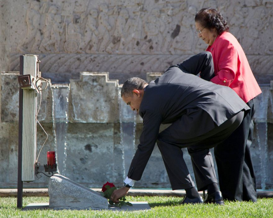 President Obama and Helen F. Chavez, widow of Cesar Chavez, places a special red rose at the Chavez grave site in Keene, Calif., on Oct. 8, 2012. (Associated Press)