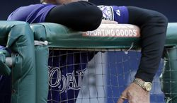 FILE - In this Sept. 9, 2012, file photo, Colorado Rockies manager Jim Tracy watches from the dugout in the first game of a baseball doubleheader against the Philadelphia Phillies in Philadelphia. The Rockies announced Sunday, Oct. 7, that Tracy has stepped down. Colorado finished last in the NL West this year and set a franchise record for losses while going 64-98. (AP Photo/Matt Slocum, File)
