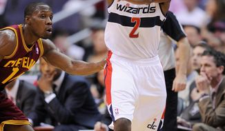 Washington Wizards guard John Wall (2) passes the ball against Cleveland Cavaliers guard Lester Hudson (14) during the first half of an NBA basketball game, Saturday, April 14, 2012, in Washington. (AP Photo/Nick Wass)