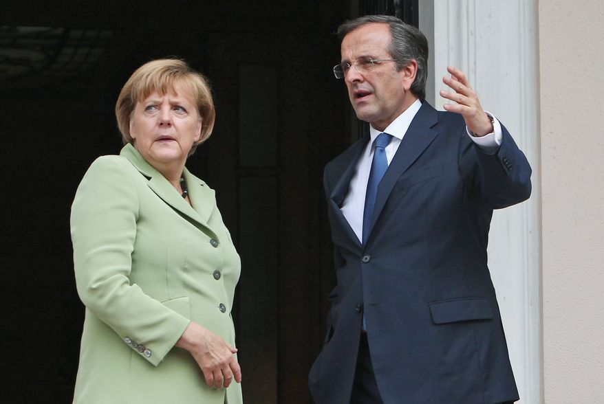 Greek Prime Minister Antonis Samaras and Mrs. Merkel speak before their meeting Tuesday at the Maximos Mansion in Athens. Amid draconian security measures and a mass protest, Mrs. Merkel was making her first visit to Greece since the eurozone crisis began there three years ago. (Associated Press)