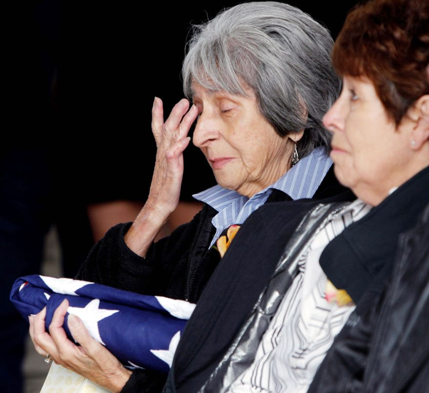 Delouise Guerra the sister of Marine  PFC James Jacques wipes away tears at his funeral at Fort Logan National Cemetery in Denver on Tuesday, Oct. 9, 2012.  The Jacques funeral was held 37 years after he was killed during the rescue of the crew of an American cargo ship seized by Cambodia in May of 1975.  His remains were identified in August 2012. Guerra's sister-in-law, Mary Lee Jacques, looks on at right.   (AP Photo/Ed Andrieski)