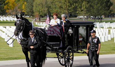 Delouise Guerra, seated right, and her sister-in-law Mary Lee Jacques ride atop a horse-drawn carriage carrying the casket at funeral services for Guerra's brother, Marine Pfc. James Jacques, at Fort Logan National Cemetery in Denver. (AP Photo/Ed Andrieski)
