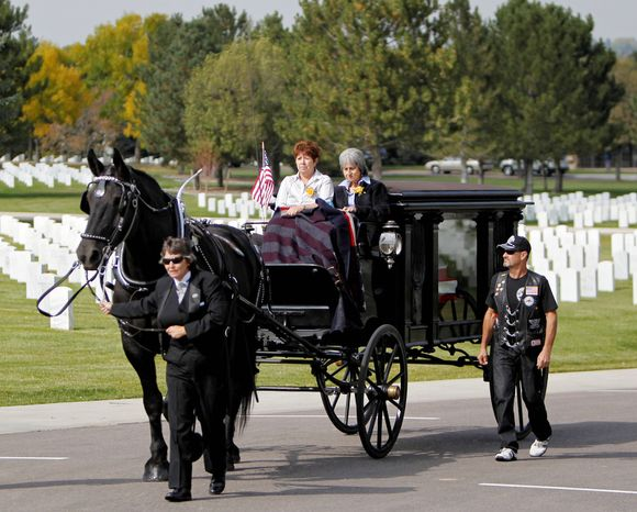 Delouise Guerra, seated right, and her sister-in-law Mary Lee Jacques ride atop a horse-drawn carriage carrying the casket at funeral services for Guerra's brother, Ma