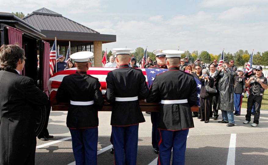 Marine honor guards remove the casket and remains of Marine  PFC James Jacques from a carriage at Fort Logan National Cemetery in Denver.  (AP Photo/Ed Andrieski)