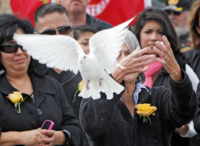 Delouise Guerra the sister of Marine PFC James Jacques releases one of 21 doves after his funeral at Fort Logan National Cemetery in Denver on Tuesday, Oct. 9, 2012. The Jacques funeral was held 37 years after he was killed during the rescue of the crew of an American cargo ship seized by Cambodia in May of 1975. His remains were identified in August 2012. (AP Photo/Ed Andrieski)
