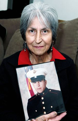 In this Oct. 5, 2012, photo Delouise Guerra poses for a photo in Denver with a 1975 photo of her younger brother,18-year-old Marine PFC James Jacques who was killed in a helicopter crash near Cambodia in 1975. Jacques remains were identified in August of this year. He will be buried with full military honors at Fort Logan National Cemetery in Denver on Tuesday, Oct. 9, 2012, on what would have been his 56th birthday. (AP Photo/Ed Andrieski)
