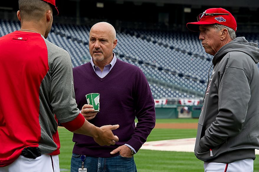 Washington Nationals general manager Mike Rizzo, center, and manager Davey Johnson, right, talk with a player during a workout session on the field at Nationals Park on Tuesday, Oct. 9, 2012. On Wednesday, they play the St. Louis Cardinals at home. (Barbara L. Salisbury/The Washington Times)