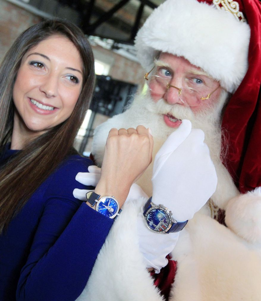 """Brady White portrays Santa Claus, right, as he and model Marisa Neira show off his and hers """"Poetic Wish"""" watches from Van Cleef & Arpels during the unveiling of the Neiman Marcus 2012 Christmas Book in Dallas, Tuesday, Oct. 9, 2012.  The Van Cleef & Arpels watches include a trip to Paris and Geneva that is priced for sale at $1,090,000.  (AP Photo/LM Otero)"""