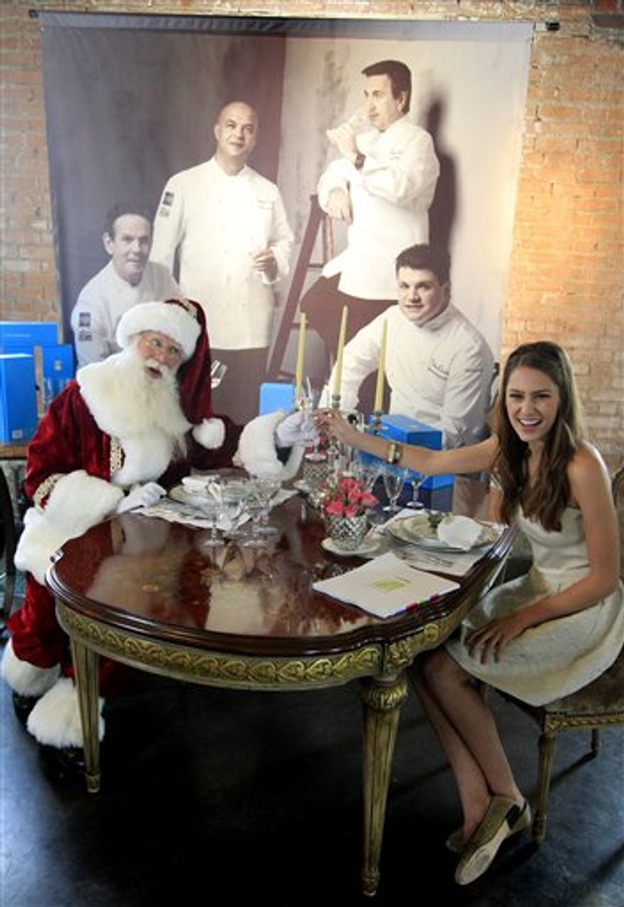 Brady White, portraying Santa Claus, left, and model Kit Johnston display the private dinner for 10 gift with four world renowned chefs preparing the meal during the unveiling of the Neiman Marcus 2012 Christmas Book in Dallas, Tuesday, Oct. 9, 2012. The meal that includes a Casa Dragones tequila tasting is priced for sale at $250,000. (AP Photo/LM Otero)