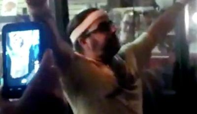 In this frame grab made from video on Friday, Oct. 5, 2012, and provided by John-Patrick McNown, Edward Archbold celebrates winning a roach-eating contest at Ben Siegel Reptile Store in Deerfield Beach, Fla. (AP Photo/Courtesy of John-Patrick McNown)