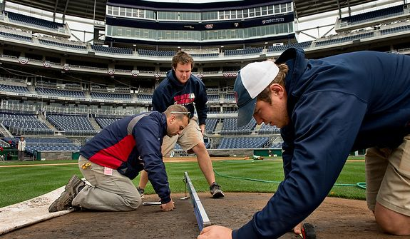 Left to right, Head Grounds Keeper John Turnour, Assistant Grounds Keeper Matt Coates, and Marty Guetting with the grounds crew conduct measurements for the pitching mound as they get ready for game 3 at Nationals Park as the Washington Nationals take on the St. Louis Cardinals in the first round of the Major League Baseball playoffs, Washington, D.C., Monday, October 8, 2012. (Andrew Harnik/The Washington Times)