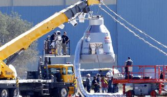 Felix Baumgartner, in pressurized suit on platform at left, prepares to enter the balloon capsule in Roswell, N.M. on Oct. 9, 2012. Baumgartner will attempt to break the speed of sound with his own body by jumping from the space capsule lifted by a 30 million cubic foot helium balloon. (Associated Press)