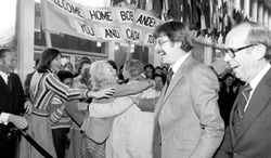 ** FILE ** A crowd at the State Department embraces Robert G. Anders, one of the six diplomats spirited out of Tehran in 1980 under the guise of a Hollywood crew member and with the help of Canadian Ambassador Ken Taylor (left). (The Associated Press)