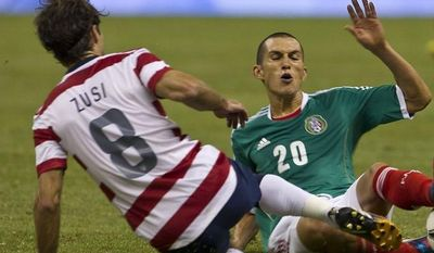 Mexico's Jorge Torres, right, fights for the ball with U.S. Graham Zusi during a friendly soccer match in Mexico City, Wednesday, Aug. 15, 2012. (AP Photo/Christian Palma)