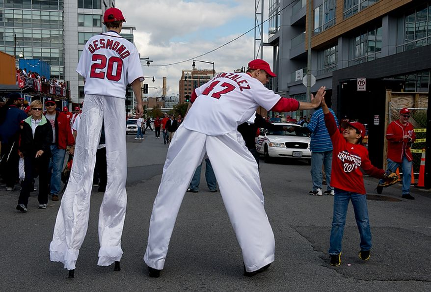 Tim Marrone, left, with Talk of the Town high-fives 8-year-old Adam Astacio of Arlington, Va. outside of Nationals Park before the first home game in the National League Division Series on Wednesday, Oct. 10, 2012. (Barbara L. Salisbury/The Washington Times)