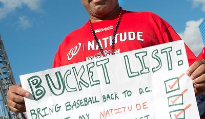"""Shellie Bowers Jr. of Washington, D.C. holds his """"Bucket List"""" sign outside of Nationals Park before the first home game in the National League Division Series on Wednesday, Oct. 10, 2012. (Barbara L. Salisbury/The Washington Times)"""