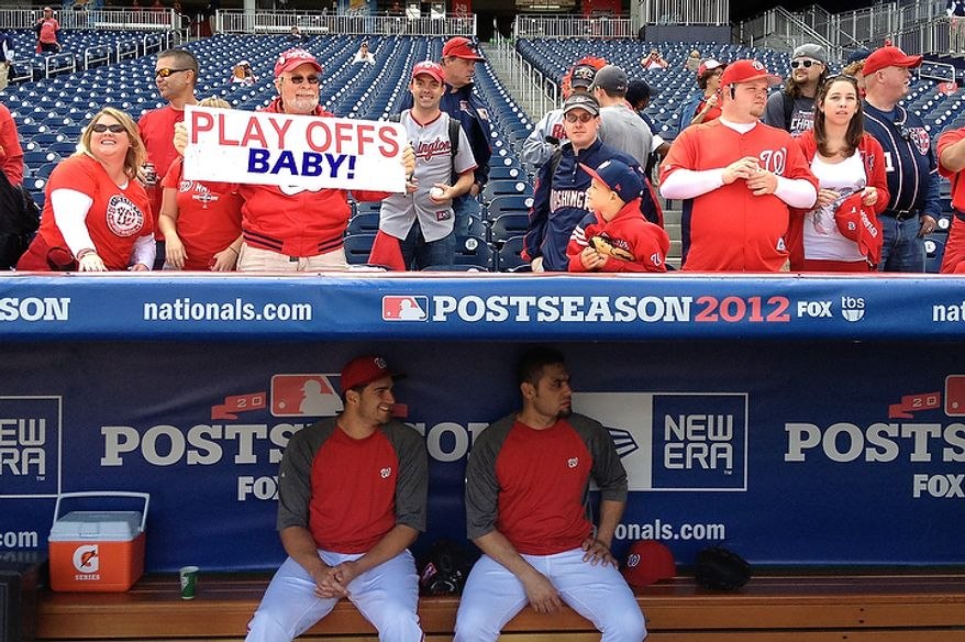 Washington Nationals relief pitchers Christian Garcia (56) and Mike Gonzalez (51) sit in the dugout before Game 3 of the National League Division Series at Nationals Park, Washington, D.C., Oct. 10, 2012. (Preston Keres/Special to The Washington Times)