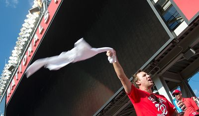 Mark Bresny of Fairfax, Va. waves a t-shirt in the air to try to rally fellow Nationals fans during the third game of the National League Division Series at Nationals Park on Wednesday, Oct. 10, 2012. (Barbara L. Salisbury/The Washington Times)