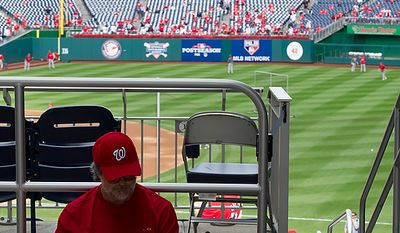 """""""I've been waiting all my life [for this],"""" says Gaithersburg resident Mike Bucci, who says he couldn't sleep last night. He got to Nationals Park when the gates opened at 10:30 a.m. on Wednesday, Oct. 10, 2012 because he had a standing-room-only ticket. Here he reads his book while waiting for the game to begin. (Barbara L. Salisbury/The Washington Times)"""