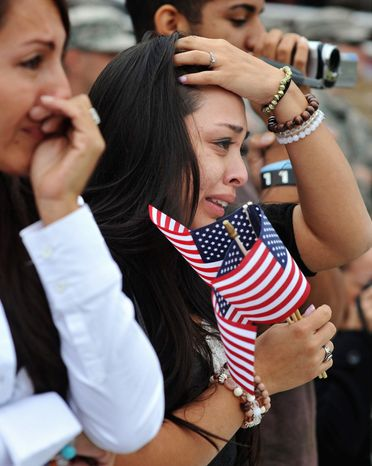 Marivel Penalea, right, reacts to seeing her fiancee  PFC Fabian Castrillon in formation during a welcome home ceremony for soldiers from the Army's 1st Battalion, 30th Infantry Regiment, Wednesday, Oct. 10, 2012 at Fort Stewart, Ga.  (AP Photo/Stephen Morton)