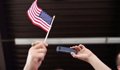 A family member waves a flag as she shoots a photo with her cell phone during a welcome home ceremony for 100 soldiers from the 1st Battalion, 30th Infantry Regiment returned home, Wednesday, Oct. 10, 2012 at Fort Stewart, Ga. (AP Photo/Stephen Morton)