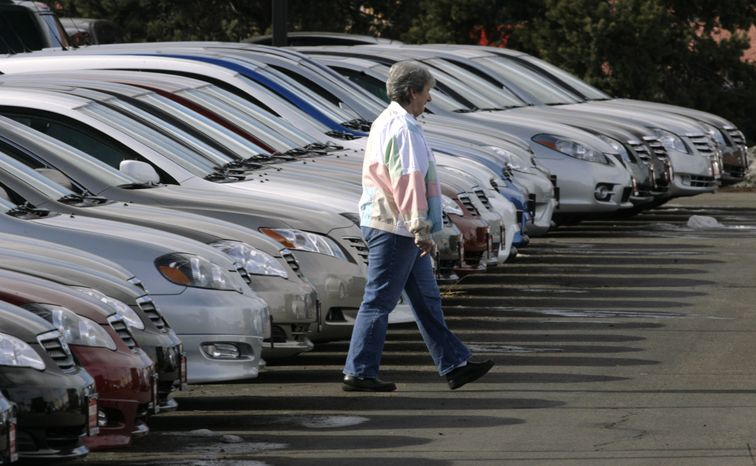 A prospective buyer searches through long lines of unsold Corolla and Camry sedans at a Toyota dealershi