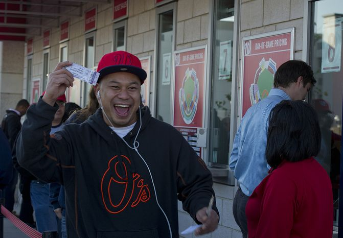 David Chheng of Herndon, Va. smiles as he holds up his ticket for the first home playoff game at Nationals Park on Wednesday, Oct. 10, 2012. He got to the stadium at 8:35 a.m. and paid $30 for the standing-room-only seat. He says he also follows the Orioles (thus the sweatshirt) and would love to see the two teams play each other. (Barbara L. Salisbury/The Washington Times)
