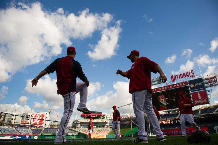 Washington Nationals left fielder Tyler Moore (left) and second baseman Stephen Lombardozzi warm up before the Nats play the St. Louis Cardinals in game three of Major League Baseball playoffs at Nationals Park in Washington on Wednesday, Oct. 10, 2012. (Andrew Harnik/The Washington Times)