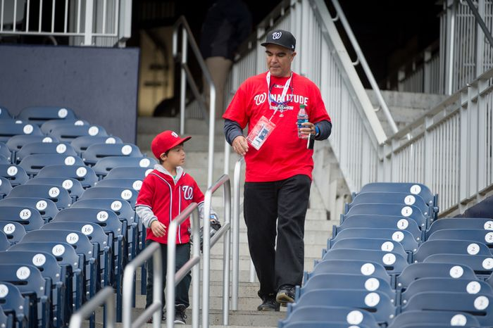 Ricardo Carmenates of Alexandria, Va., and his son, R.J., 7, make their way into the stadium before the Washington Nationals play the St. Louis Cardinals in game three of Major League Baseball playoffs at Nationals Park in Washington on Wednesday, Oct. 10, 2012. (Andrew Harnik/The Washington Times)
