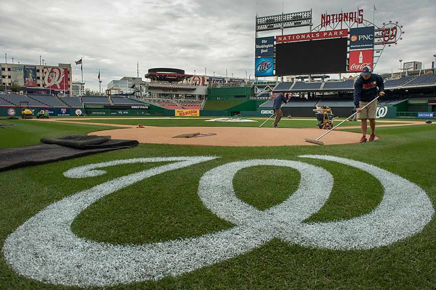 Marty Guetting (right), with the grounds crew, smooths out dirt at home plate as the groundskeepers get ready for the playoff games between the Washington Nationals and the St. Louis Cardinals at Nationals Park in Washington on Monday, Oct. 8, 2012. (Andrew Harnik/The Washington Times)