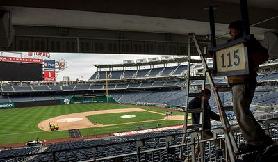 Stadium workers Peter Gabauer (right) and Wes Snyder (bottom left) take down a sign to make way for an extra camera platform along the third base stands as crews get ready for game 3 at Nationals Park as the Washington Nationals take on the St. Louis Cardinals in the first round of the Major League Baseball playoffs in Washington on Monday, Oct. 8, 2012. (Andrew Harnik/The Washington Times)