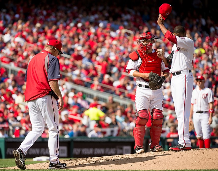 A Washington Nationals pitching coach comes to the mound to talk to Washington Nationals starting pitcher Edwin Jackson (33) after struggling in the second inning as the Washington Nationals play the St. Louis Cardinals in game three of Major League Baseball playoffs at Nationals Park, Washington, D.C., Wednesday, October 10, 2012. (Andrew Harnik/The Washington Times)