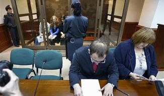 Feminist punk group Pussy Riot members, from left, Maria Alekhina, Yekaterina Samutsevich and Nadezhda Tolokonnikova sit in a glass cage at a court room in in Moscow, Wednesday, Oct. 10, 2012. Lawyers Violetta Volkova, right, and Lev Lyalin, foreground center, defending members of feminist punk group Pussy Riot, sit in front. (AP Photo/Sergey Ponomarev)