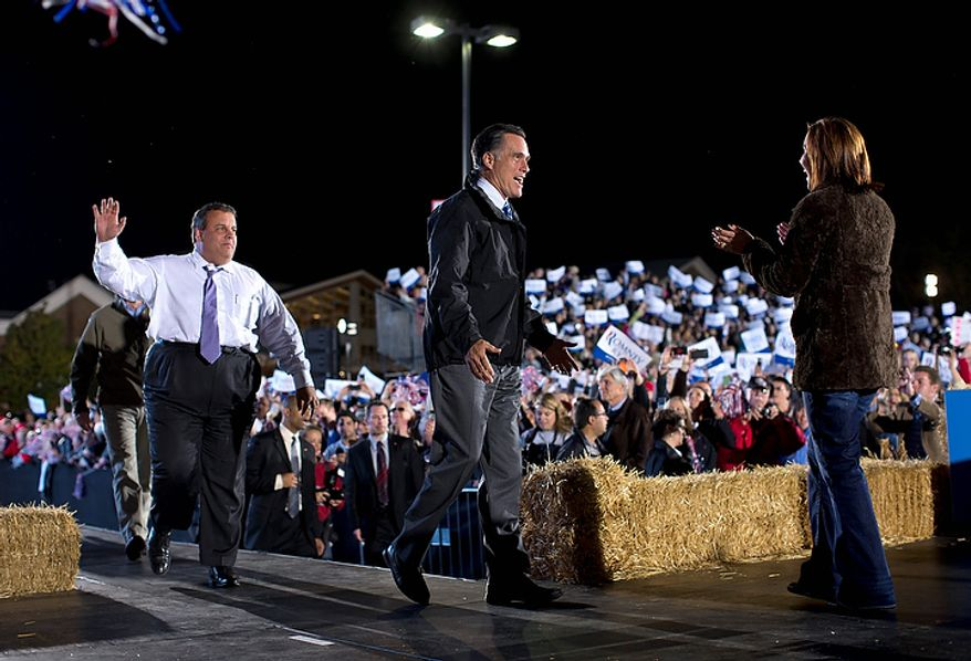 Republican presidential candidate Mitt Romney (center) and New Jersey Gov. Chris Christie (left) arrive at a campaign rally after being introduced by Ohio Lt. Gov. Mary Taylor on Tuesday, Oct. 9, 2012, in Cuyahoga Falls, Ohio. (AP Photo/Evan Vucci)