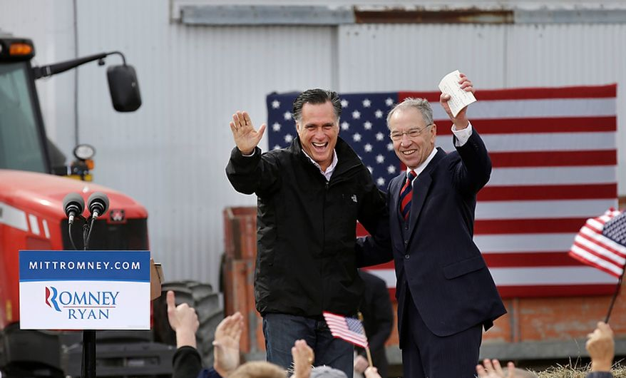 Republican presidential candidate Mitt Romney and Sen. Chuck Grassley (right), Iowa Republican, wave before Mr. Romney spoke at a campaign stop at the Koch family farm on Tuesday, Oct. 9, 2012, in Van Meter, Iowa. (AP Photo/Charlie Neibergall)
