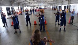 **FILE** Wellness coach Kara Whitcomb (front center) leads truckers in a stretching regime before their driving shifts start at Con-way Freight in Garland, Texas, on July 11, 2012. (Associated Press)
