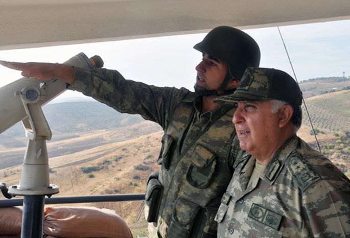 Turkish Chief of Staff Gen. Necdet Ozel (right) listens Oct. 9, 2012, to a commander during his tour of the military along the border with Syria in Hatay, Turkey. (Associated Press/Turki