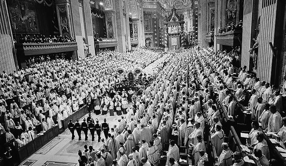 Roman Catholic prelates stand as Pope Paul VI, on portable throne, is escorted through the main nave of St. Peter's Basilica in Vatican City to address the last meeting of the Ecumenical Council's second session,  Dec. 4, 1963.  The pontiff recessed the council for nine months after urging prelates to share with him in governing the Church. (AP Photo)