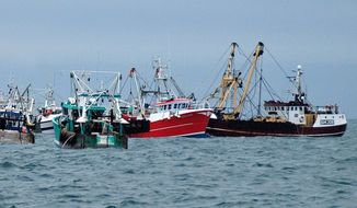 British fishing boats (center and right) are prevented from fishing by French fishermen in the English Channel off Le Havre, western France, on Monday. A bumper season for scallops has given rise to a bitter international dispute in the channel. (Associated Press)