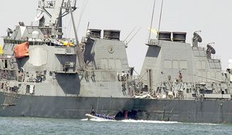 ** FILE ** Investigators in a speedboat examine the hull of the USS Cole at the Yemeni port of Aden in October 2000. An explosion detonated by terrorists in a small boat had breached the hull of the destroyer while in port, killing 17 sailors and injuring 39. (Associated Press)